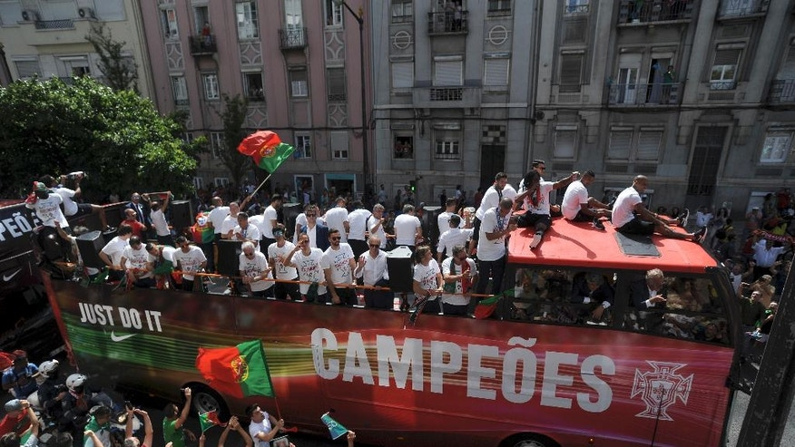 Portugal's soccer team with the Euro 2016 trophy take part in a bus parade in Lisbon, Portugal, Monday, July 11, 2016. Hundreds of thousands of jubilant people lined the sunbaked streets of the Portuguese capital on Monday to greet the national football team after they arrived back from winning the European Championship, its first major trophy.  (AP Photo/Paulo Duarte)