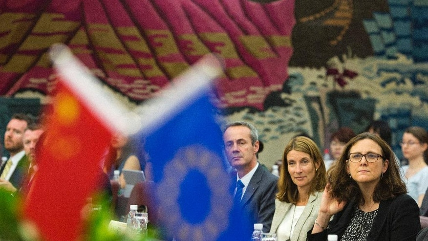 EU Trade Commissioner Cecilia Malmstrom, right, prepares to speak at the University of International Business and Economics in Beijing Monday, July 11, 2016. Malmstrom said China has to give European companies the same kind of market access that Chinese companies enjoy in Europe before discussions can start on a bilateral free trade agreement. (AP Photo/Ng Han Guan)