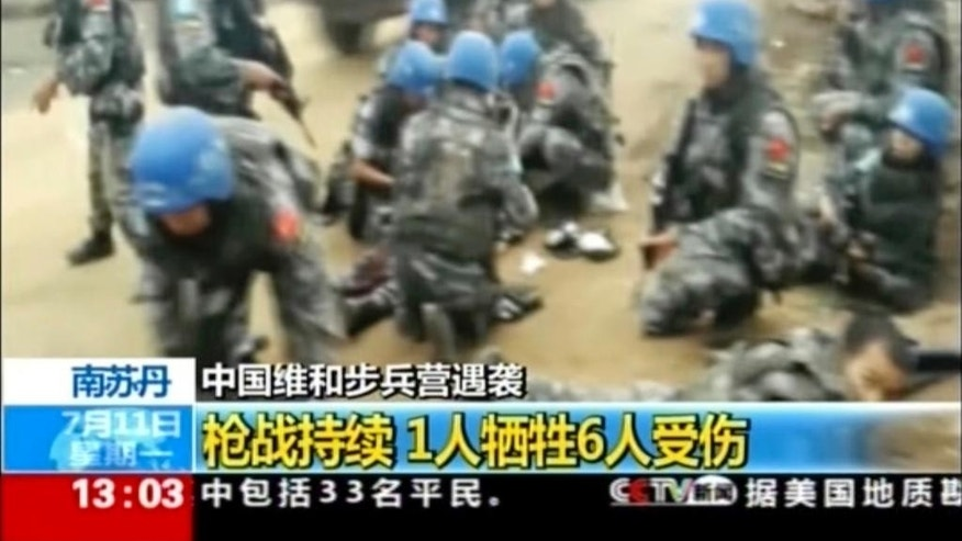 In this image taken from a July 10, 2016 video footage released by China's CCTV via AP Video, Chinese UN peacekeepers tend to their wounded colleagues after an attack on an armored personal carrier used by the Chinese peacekeepers in Jebel in South Sudan. Heavy explosions are shaking South Sudan's capital Juba Monday, July 11, 2016, as clashes between government and opposition forces entered their fifth day, witnesses say, pushing the country back toward civil war. (CCTV via AP Video)