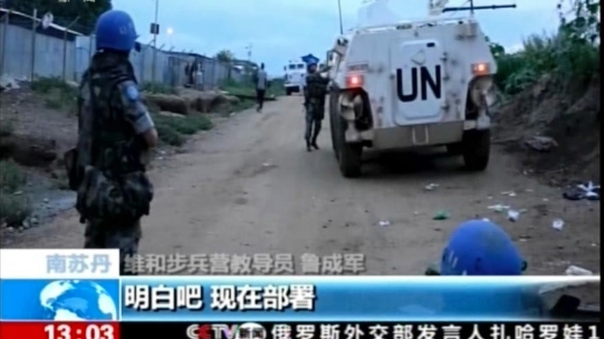 In this image taken from a July 10, 2016 video footage released by China's CCTV via AP Video, Chinese UN peacekeepers tend to a wounded colleague after an attack on an armored personal carrier used by the Chinese peacekeepers in Jebel in South Sudan. Heavy explosions are shaking South Sudan's capital Juba Monday, July 11, 2016, as clashes between government and opposition forces entered their fifth day, witnesses say, pushing the country back toward civil war. (CCTV via AP Video)