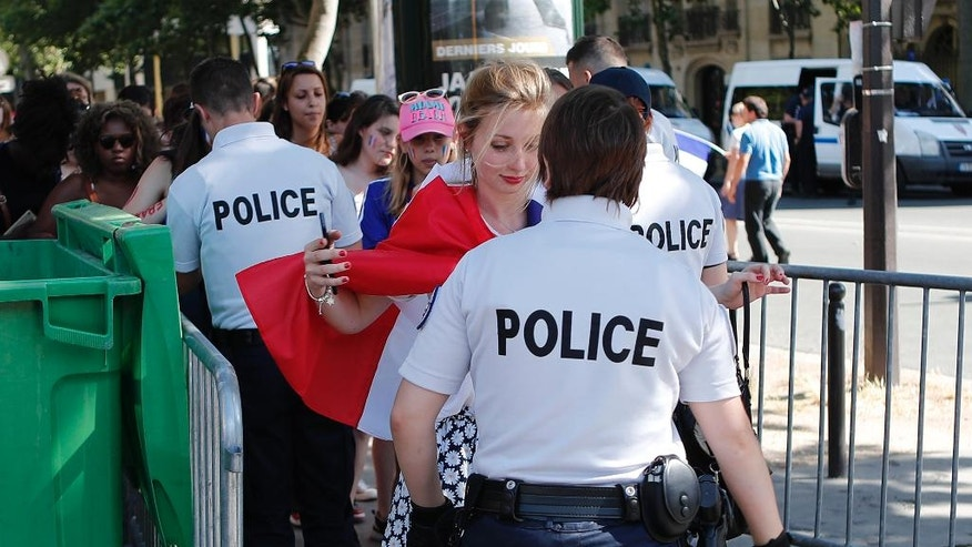 French police officers search supporters before entering the Paris fan zone, hours before the Euro 2016 final soccer match between Portugal and France, Sunday, July 10, 2016 in Paris. (AP Photo/Francois Mori)
