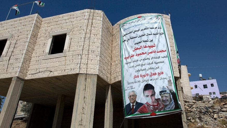 "This Saturday, July 9, 2016 photo, shows a banner, with pictures of the late Palestinian leader Yasser Arafat, President Mahmoud Abbas and Mohammed Tarayreh, 17, who was killed after breaking into a Jewish settlement on June 30 and stabbing a 13 year-old Israeli girl to death, displayed on a building in the Tarayreh family's West Bank village of Bani Na'im, near Hebron. The Tarayreh family is now eligible for $350 a month from a Palestinian ""Martyrs' Fund."" They have also received a notice ordering the demolition of their two-story villa, a standard Israeli retribution for attacks. Arabic on the poster in part reads, ""Palestinian National Liberation Movement, Fatah, celebrates its martyr hero Mohammed Tarayreh."" (AP Photo/Nasser Nasser)"