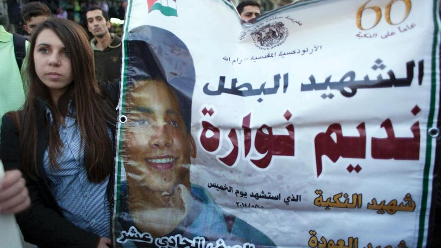 "FILE -- In this Thursday, Nov. 20, 2014 file photo, a Palestinian student holds a banner with a picture of Nadim Nuwara, and phrases that read, ""Nakba Martyr, hero, an eleventh grade student,"" who died during clashes in the West Bank along with another youth, Mohammad Abu Daher, in May 2014, in the West Bank city of Ramallah. To Palestinians, the ""Martyrs' Fund"" has helped generations of needy families whose relatives have been killed, jailed or wounded in fighting with Israel. To Israel, the fund actually promotes violence by rewarding the families of attackers. (AP Photo/Nasser Nasser, File)"