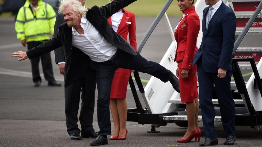 Virgin boss Richard Branson with Virgin Atlantic staff after they arrive aboard a new Airbus A350 at the Farnborough International Airshow in Farnorough, south England, Monday July 11, 2016.  Britain has signed a contract for nine new P-8A Poseidon military aircraft, and Boeing announced Monday a planned expansion for its British operation, as the airshow attracts large international companies to announce their latest plans. (Andrew Matthews / PA via AP)