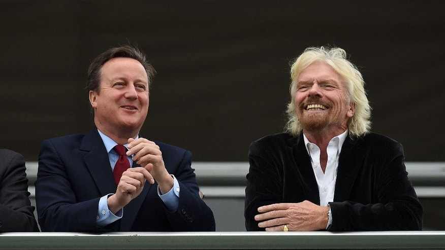 Britain's Prime Minister David Cameron, left, and Virgin boss Richard Branson at the Farnborough International Airshow in Farnorough, south England, Monday July 11, 2016.  Britain has signed a contract for nine new P-8A Poseidon military aircraft, and Boeing announced Monday a planned expansion for its British operation, as the airshow attracts large international companies to announce their latest plans. (Andrew Matthews / PA via AP)