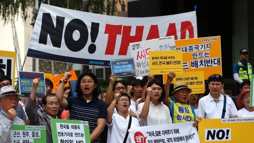 "South Koreans shout slogans during a rally to denounce deploying the Terminal High-Altitude Area Defense, or THAAD, near U.S. Embassy in Seoul, South Korea, Monday, July 11, 2016. Seoul and Washington launched formal talks on deploying the Terminal High-Altitude Area Defense, or THAAD, after North Korea conducted a nuclear test and a long-range rocket launch earlier this year. China, Russia and North Korea all say the THAAD deployment could help U.S. radars spot missiles in their countries. The letters read ""Oppose, Deploy the Terminal High-Altitude Area Defense, or THAAD."" (AP Photo/Lee Jin-man)"