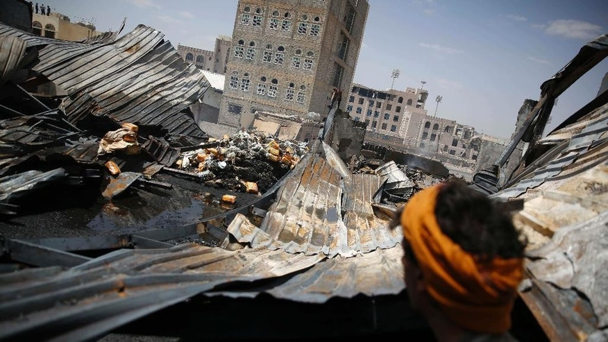 FILE - In this Thursday, Sept. 17, 2015, file photo, a worker looks at a chocolate factory destroyed by a Saudi-led airstrike in Sanaa, Yemen. Businesses worth millions of dollars have sustained major destruction in Yemen's year-long conflict either by the Saudi-led coalition targeting Shiite rebels or ground fighting and random shelling by the rival parties, an international rights group said Monday. (AP Photo/Hani Mohammed)