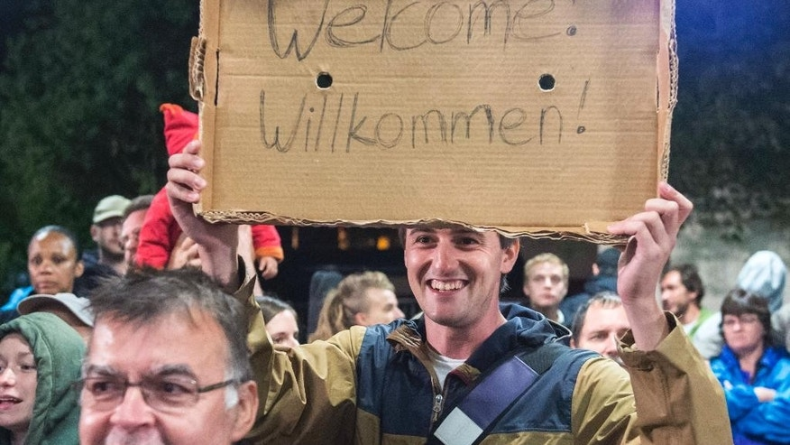 FILE - In this Sept. 5, 2015 file picture a man holds a cardboard with a 'Welcome' slogan during the arrival of refugees at the train station in Saalfeld, central Germany.  The refugee crisis and the threat of terrorism in Europe are very much related to one another in the minds of many Europeans, according to a survey conducted  by the Pew Research Center across the continent. Many Europeans also worry that migrants will become an economic burden and take away their jobs and social benefits. Populist parties all over the continent have successfully increased their numbers by campaigning against Muslim migrants including the right-wing Alternative for Germany or Austria's Freedom Party.   (AP Photo/Jens Meyer,file)