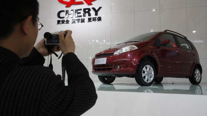 FILE - In this April 20, 2007 file photo, a man takes a picture of a car from Chinese automaker Chery during the Shanghai Auto Show in Shanghai, China.  India has the most transparent companies while Chinese firms are the most opaque, according to a global anti-graft watchdog's survey released Monday, July 11, 2016, that assesses efforts by emerging market companies to fight corruption.  Thirty-seven Chinese companies were evaluated, making them the survey's biggest group, but they had the weakest overall performance. The three companies that scored zero out of 10 were all Chinese, which includes automaker Chery. (AP Photo/Ng Han Guan, File)