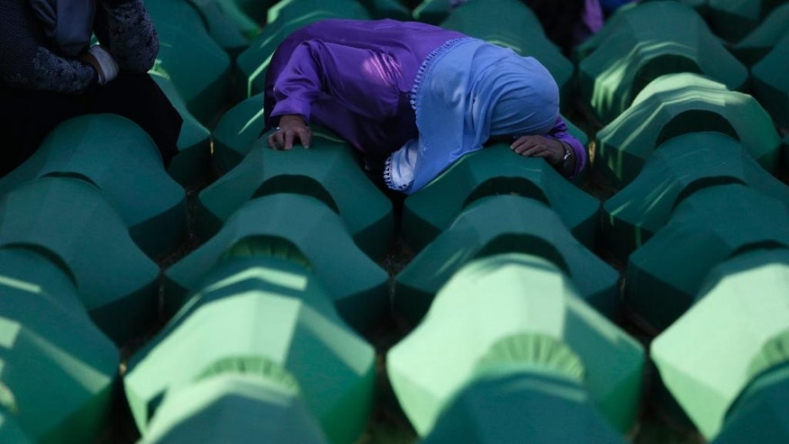 A Bosnian woman prays next to a coffin containing the remains of her relative perished in the Srebrenica massacre, during a funeral ceremony for the 127 victims at the Potocari memorial complex near Srebrenica, 150 kilometers (94 miles) northeast of Sarajevo, Bosnia and Herzegovina, Monday, July 11, 2016. Twenty one years ago, on July 11, 1995, Serb troops overran the eastern Bosnian Muslim enclave of Srebrenica and executed some 8,000 Muslim men and boys. (AP Photo/Amel Emric)