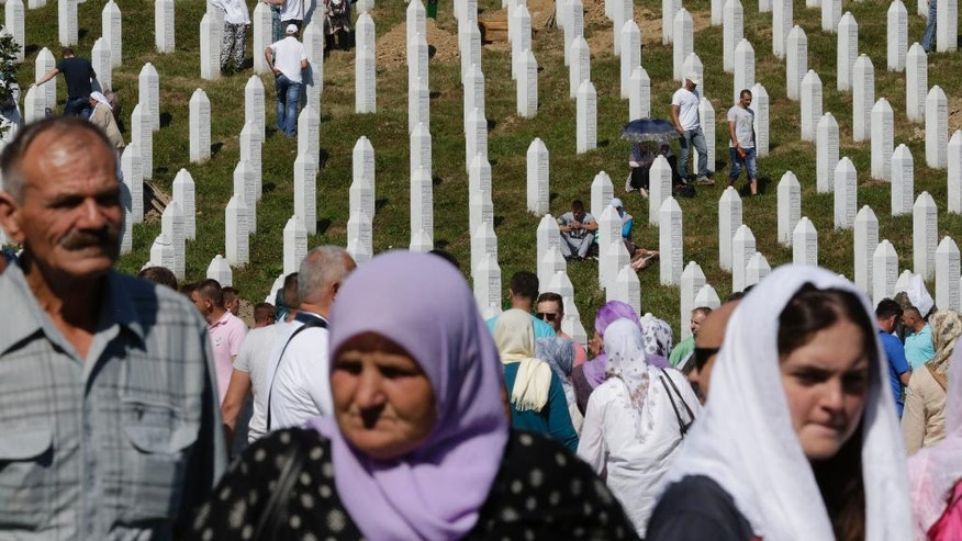 Bosnian people stand near coffins containing the remains of people killed during Srebrenica massacre, during a funeral ceremony for the 127 victims at the Potocari memorial complex near Srebrenica, 150 kilometers (94 miles) northeast of Sarajevo, Bosnia and Herzegovina, Monday, July 11, 2016. Twenty one years ago, on July 11, 1995, Serb troops overran the eastern Bosnian Muslim enclave of Srebrenica and executed some 8,000 Muslim men and boys. (AP Photo/Amel Emric)
