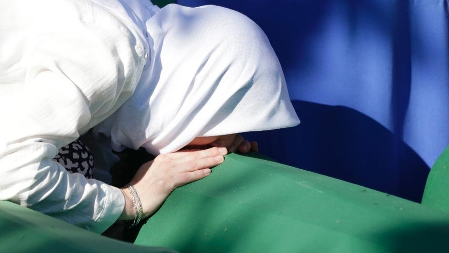 A Bosnian woman prays next to a coffin containing the remains of her relative perished in the Srebrenica massacre, during a funeral ceremony for the 127 victims at the Potocari memorial complex near Srebrenica, 150 kilometers (94 miles) northeast of Sarajevo, Bosnia and Herzegovina, Monday, July 11, 2016. Twenty one years ago, on July 11, 1995, Serb troops overran the eastern Bosnian Muslim enclave of Srebrenica and executed some 8,000 Muslim men and boys, which International courts have labeled as an act of genocide. (AP Photo/Amel Emric)