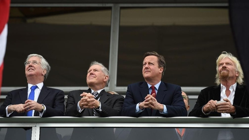 Prime Minister David Cameron, second right, and Virgin boss Richard Branson, right, with Britian's Defence Secretary Michael Fallon, left, at the Farnborough International Airshow in Farnorough, south England, Monday July 11, 2016.  Britain has signed a contract for nine new P-8A Poseidon military aircraft, and Boeing announced Monday a planned expansion for its British operation, as the airshow attracts large international companies to announce their latest plans. (Andrew Matthews / PA via AP)