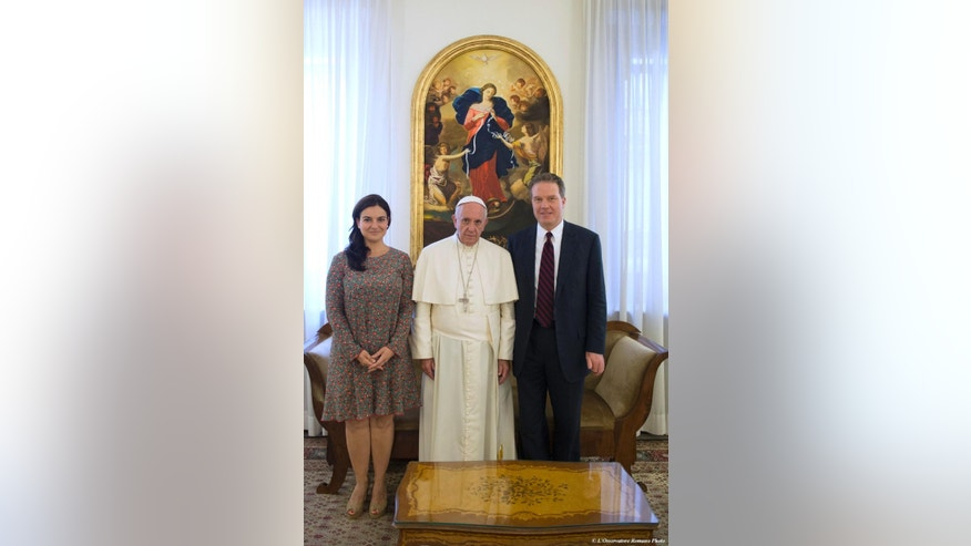 Pope Francis poses for a family picture with Greg Burke and Paloma Garcia Ovejero at the Vatican, Monday, July 11, 2016. Pope Francis has named a former Fox TV correspondent, Greg Burke, to replace his longtime spokesman and tapped Paloma Garcia Ovejero, of Spain, to be his deputy, the first time a woman has held the post. (L'Osservatore Romano/Pool photo via AP)