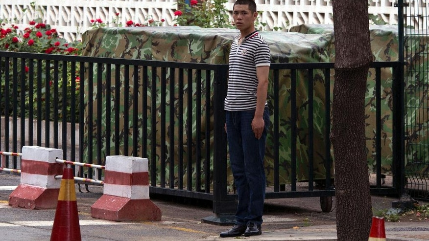 A plainclothes security person stands on duty outside the Philippines embassy in Beijing Tuesday, July 12, 2016. A tribunal ruled on a case raised by the Philippines in a sweeping decision Tuesday that China has no legal basis for claiming much of the South China Sea and had aggravated the seething regional dispute with its large-scale land reclamation and construction of artificial islands that destroyed coral reefs and the natural condition of the disputed areas. (AP Photo/Ng Han Guan)