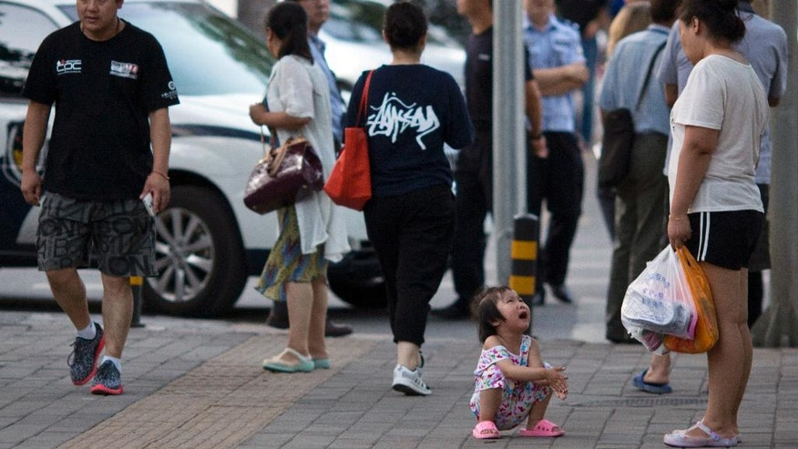 A child cries near a police road block leading to the Philippines embassy in Beijing Tuesday, July 12, 2016. A tribunal ruled on a case raised by the Philippines in a sweeping decision Tuesday that China has no legal basis for claiming much of the South China Sea and had aggravated the seething regional dispute with its large-scale land reclamation and construction of artificial islands that destroyed coral reefs and the natural condition of the disputed areas. (AP Photo/Ng Han Guan)