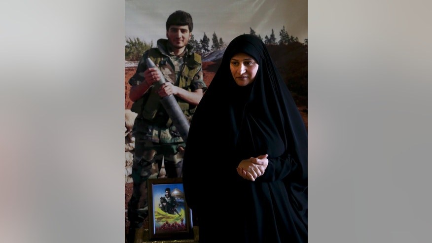 In this Wednesday, June 29, 2016 photo, Hanan Ibrahim, the mother of slain Hezbollah fighter Khalil Ibrahim, portrayed behind, who was killed in a Damascus suburb known as Ghouta, on Dec. 27, 2013, speaks during an interview with The Associated Press at her home in the southern village of Aynata, close to the town of Bint Jbail, Lebanon. A decade after it fought Israel in a devastating month-long war, the Iran-backed Shiite Hezbollah is in crisis, having been forced to join an unpopular, costly war to defend President Bashar Assad against rebels. (AP Photo/Hassan Ammar)