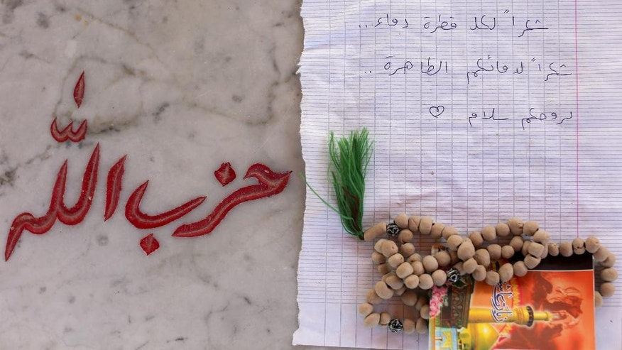 """In this Wednesday, June 29, 2016, photo, a letter reads in Arabic, """"Thank you for each drop of blood. Thanks for your pure blood. Peace for your souls."""" and prayer beads left by a supporter of Hezbollah on the grave of Mahdi Daqiq, who was killed on Aug. 14, 2006 during fighting with Israel in 2006 war, in the southern village of Harees, close to the town of Bint Jbail, Lebanon. Arabic on the grave reads, """"Hezbollah."""" A decade after it fought Israel in a devastating month-long war, the Iran-backed Shiite Hezbollah is in crisis, having been forced to join an unpopular, costly war to defend President Bashar Assad against rebels. (AP Photo/Hassan Ammar)"""