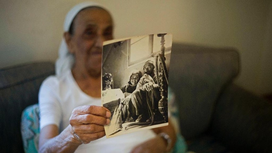 This Monday, July 11, 2016, photo shows Yemen born Jewish Israeli Yona Josef holding a photograph dated back to the 1940's of her and her father back in Yemen in her home in Raanana, Israel. Josef said she was asked to take her 4-year-old sister Saada to a health clinic and leave her there. When she returned several hours later, she was told her sister was dead and the family was given no further details or a body to bury. The stories have been circulating in Israel for decades: Newborn babies of Jewish immigrants from Arab countries mysteriously disappeared shortly after arriving in the country, purportedly snatched away and given to childless couples.  (AP Photo/Ariel Schalit)