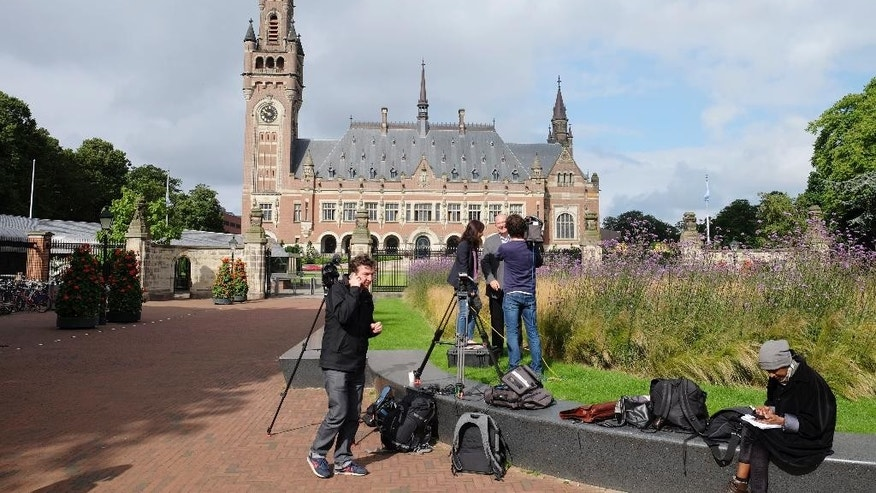 Journalists gather outside the Peace Palace in The Hague, Netherlands, on Tuesday, July 12, 2016, ahead of a ruling by the Permanent Court of Arbitration (PCA) on the dispute between China and the Philippines over the South China Sea. China has intensified the drumbeat of its opposition to an international tribunal's ruling expected Tuesday that could threaten its expansive claims in the South China Sea. (AP Photo/Mike Corder)