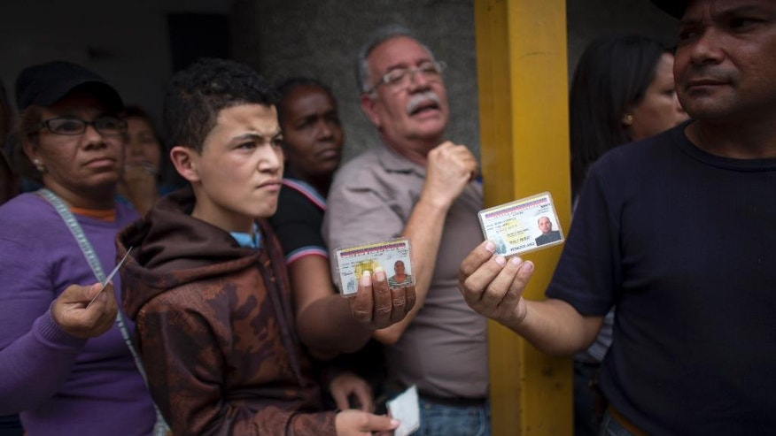 In this Tuesday, May 3, 2016 photo, people show their national ID cards as they wait in line outside a supermarket to buy food in Caracas, Venezuela. All Venezuelans, including children, are assigned two shopping days a week based on their state ID number. Some use fake IDs to score extra shopping days. (AP Photo/Ariana Cubillos)