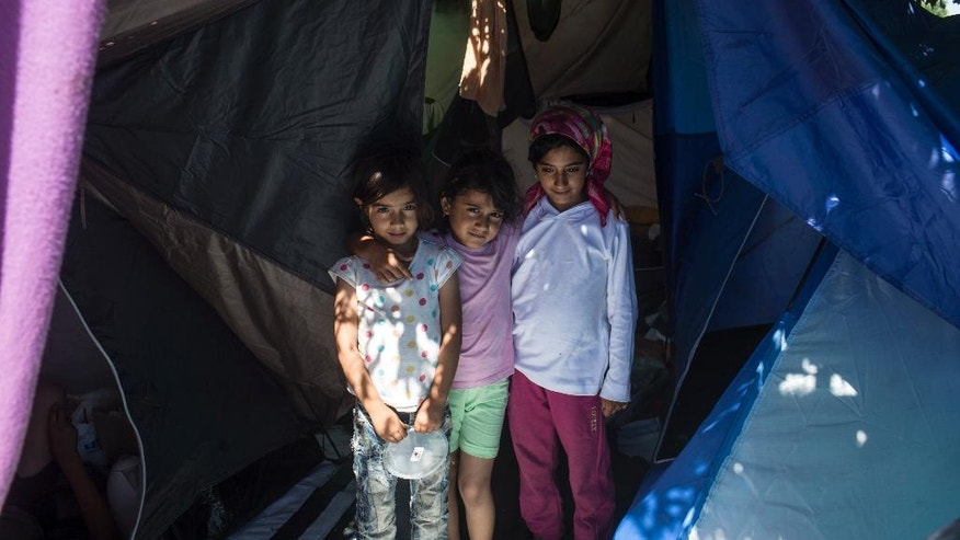 Children stand in a tent inside a migrant camp at Serbia's border with Hungary, in Horgos, Serbia, Monday, July 11, 2016. In what appears to be another refugee crisis in the making in Europe, the numbers are surging at camps on Serbia's border with EU country Hungary. The numbers have been growing since last week, when Hungary introduced forced deportations of migrants caught within 8 kilometers (5 miles) of border fences. (AP Photo/Marko Drobnjakovic)
