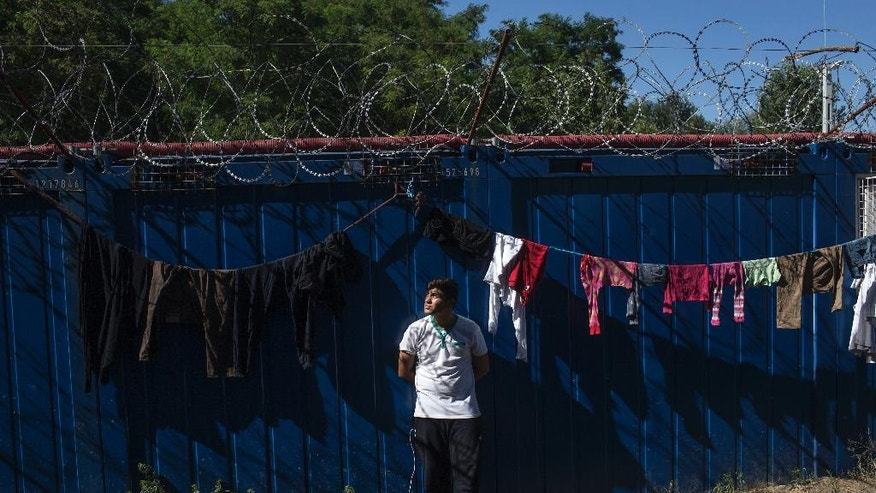 A man stands next to drying laundry inside a migrant camp at Serbia's border with Hungary, in Horgos, Serbia, Monday, July 11, 2016. In what appears to be another refugee crisis in the making in Europe, the numbers are surging at camps on Serbia's border with EU country Hungary. The numbers have been growing since last week, when Hungary introduced forced deportations of migrants caught within 8 kilometers (5 miles) of border fences. (AP Photo/Marko Drobnjakovic)