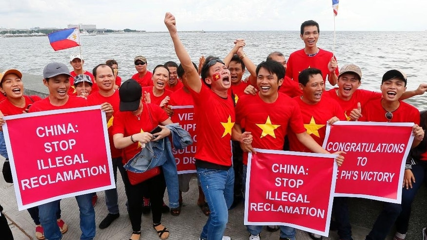 Vietnamese expatriates cheer while displaying placards during a rally by the Manila's baywalk before the Hague-based U.N. international arbitration tribunal is to announce its ruling on South China Sea Tuesday, July 12, 2016, Philippines. The Vietnamese are supporting the Philippines' case it filed before the international tribunal on China's nine-dash line claim in the South China Sea. (AP Photo/Bullit Marquez)