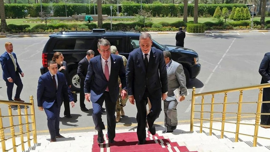 Visiting U.S. Defense Secretary Ash Carter, center left, accompanied by the Iraqi Defense Minister Khaled al-Obeidi, center right, arrives to the Ministry of Defense in Baghdad, Iraq, Monday, July 11, 2016. As Carter arrived in Iraq, Monday, he said U.S. and coalition forces will use the newly retaken air base in Qayara as a staging hub as Iraqi security forces move closer to the long-awaited battle to recapture Mosul from Islamic State militants. Carter landed in Baghdad on an unannounced visit and says U.S. advisers are prepared to accompany Iraqi battalions, if needed, as those units move closer to the fight for Mosul. (AP Photo)