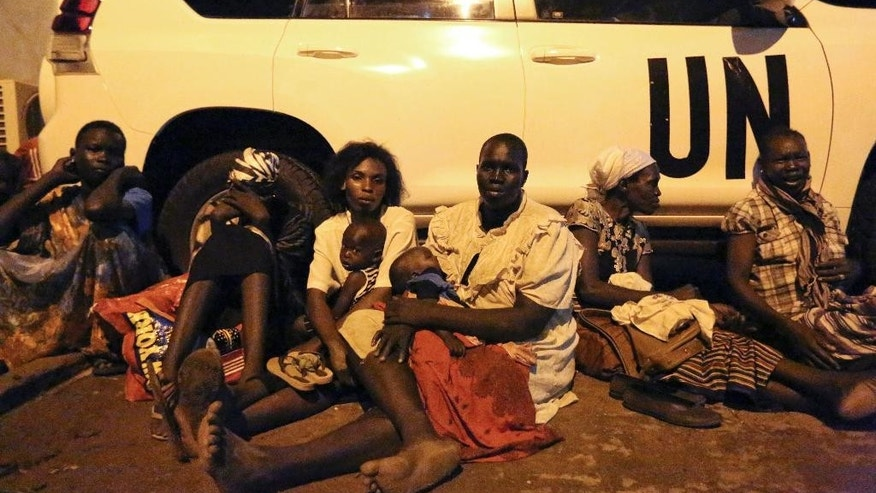 In this photo taken late Friday, July 8, 2016 and released by the United Nations Mission in South Sudan (UNMISS), women from neighboring villages rest against a UN vehicle as they take cover from the fighting between buildings on the perimeter of the UN base and compound in the capital Juba, South Sudan. The president of South Sudan and his opposition rival both called Monday for a cease-fire in a conflict that has seen fierce clashes between their forces spread from the capital to a southeastern town. (Eric Kanalstein/UNMISS via AP)