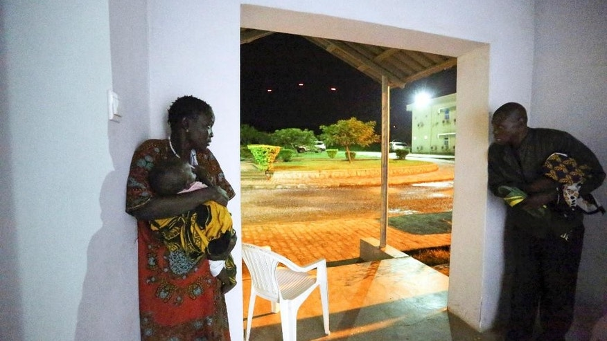 In this photo taken late Friday, July 8, 2016 and released by the United Nations Mission in South Sudan (UNMISS), a man, woman and infant take cover in the doorway of the UN offices as fighting starts with tracers flying by in the sky near the perimeter of the UN base and compound in the capital Juba, South Sudan. The president of South Sudan and his opposition rival both called Monday for a cease-fire in a conflict that has seen fierce clashes between their forces spread from the capital to a southeastern town. (Eric Kanalstein/UNMISS via AP)