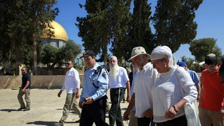 The parents of Hallel Yaffa Ariel walk near the Dome of the Rock Mosque in the Al Aqsa Mosque compound in Jerusalem's Old City, Tuesday, July 12, 2016. Family members of a slain Jewish teenager have made a high-profile pilgrimage to a sensitive Jerusalem holy site. Police spokesman Micky Rosenfeld says some 80 relatives of Hallel Yaffa Ariel visited the Temple Mount Tuesday, a sacred spot also known to Muslims as the Noble Sanctuary. Ariel, 13, was stabbed to death while she slept in her bed in the Kiryat Arba settlement last month. The visit passed without incident. (AP Photo/Mahmoud Illean)