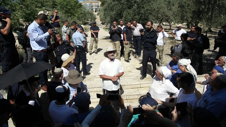 The father of Hallel Yaffa Ariel walks near the Dome of the Rock Mosque in the Al Aqsa Mosque compound in Jerusalem's Old City, Tuesday, July 12, 2016. Family members of a slain Jewish teenager have made a high-profile pilgrimage to a sensitive Jerusalem holy site. The visit passed without incident.(AP Photo/Mahmoud Illean)