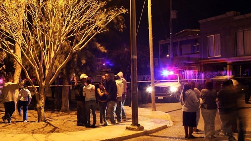 JUAREZ, MEXICO - MARCH 25:  Residents look out at a crime scene involving the killing of a 13 year old boy in a car, one of numerous murders over a 24 hour period, on March 25, 2010 in Juarez, Mexico. Secretary of State Hillary Rodham Clinton, Defense Secretary Robert Gates, and Homeland Security Secretary Janet Napolitano all visited Mexico on March 23 for discussions centered on Mexico's endemic drug-related violence. The border city of Juarez, Mexico has been racked by violent drug related crime recently and has quickly become one of the most dangerous cities in the world to live. As drug cartels have been fighting over ever lucrative drug corridors along the United States border, the murder rate in Juarez has risen to 173 slayings for every 100,000 residents. President Felipe Calderon's strategy of sending 7000 troops to Juarez has not mitigated the situation. With a population of 1.3 million, 2,600 people died in drug-related violence last year and 500 so far this year, including two Americans recently who worked for the U.S. Consulate and were killed as they returned from a children's party.  (Photo by Spencer Platt/Getty Images)