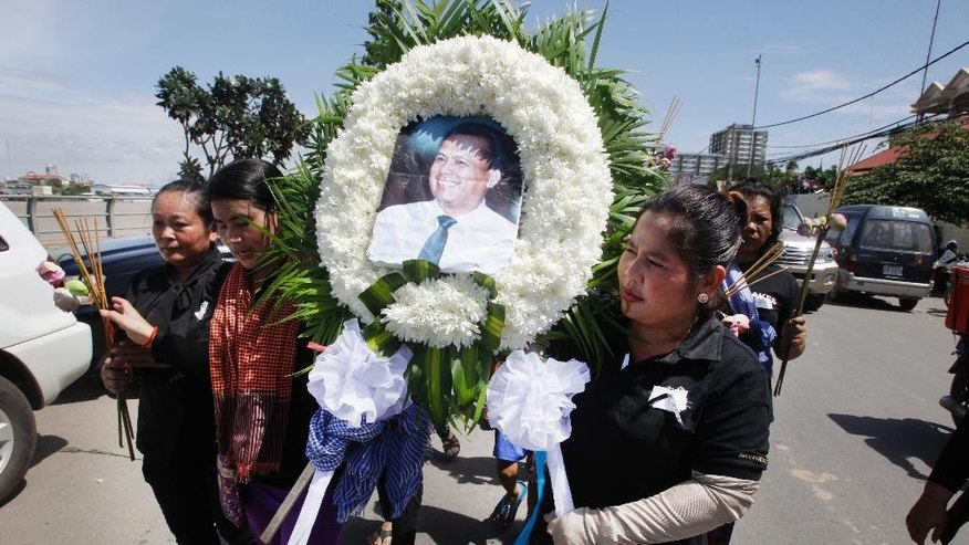 FILE - In this July 11, 2016 file photo, Cambodian community activists carry a wreath during the funeral procession of government critic Kem Ley, pictured, in Phnom Penh, Cambodia.  Oeut Ang, the man who allegedly shot dead Kem Ley over what he claimed was a money dispute is too poor to have loaned the victim $3,000, his wife said Tuesday, July 12, 2016. (AP Photo/Heng Sinith, File)
