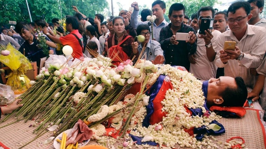 FILE - In this July 11, file photo, the body of Cambodian government critic Kem Ley is covered by the Cambodian National flag as flowers are placed during a funeral ceremony in Phnom Penh, Cambodia. Oeut Ang, the man who allegedly shot dead Kem over what he claimed was a money dispute, is too poor to have loaned the victim $3,000, his wife said Tuesday. (AP Photo/Heng Sinith, File)