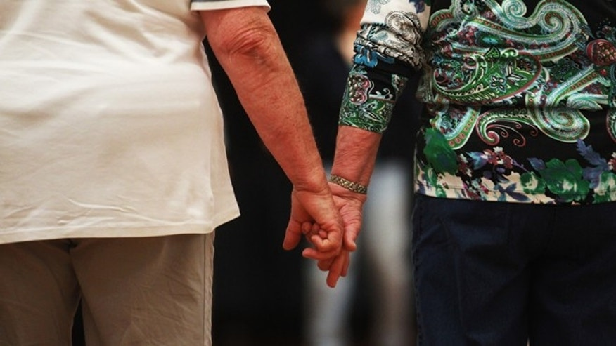 "HAMBURG, GERMANY - MAY 03:  An elderly couple hold hands at a trade fair at the ""Seniorentag 2012"" senior citizens convention on May 3, 2012 in Hamburg, Germany. The three-day long convention caters specifically to the needs of elderly people, who in Germany, as in the rest of Europe, are becoming an increasingly higher portion of the overall population. Europe as a whole, through its low birth rates and improving health care, is undergoing a demographic shift that has far-reaching consequences for labor markets, public policy planning and government budgets.  (Photo by Joern Pollex/Getty Images)"