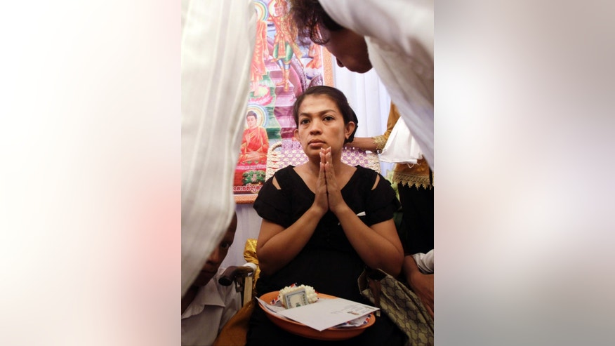 Phou Ratana, wife of Cambodia's prominent government critic Kem Ley, prays as mourners share some donations during a funeral ceremony in Phnom Penh, Cambodia, Wednesday, July 13, 2016. A former Cambodian soldier has been charged with murder in the killing of Kem Ley, an attack that has raised accusations of a political conspiracy. (AP Photo/Heng Sinith)