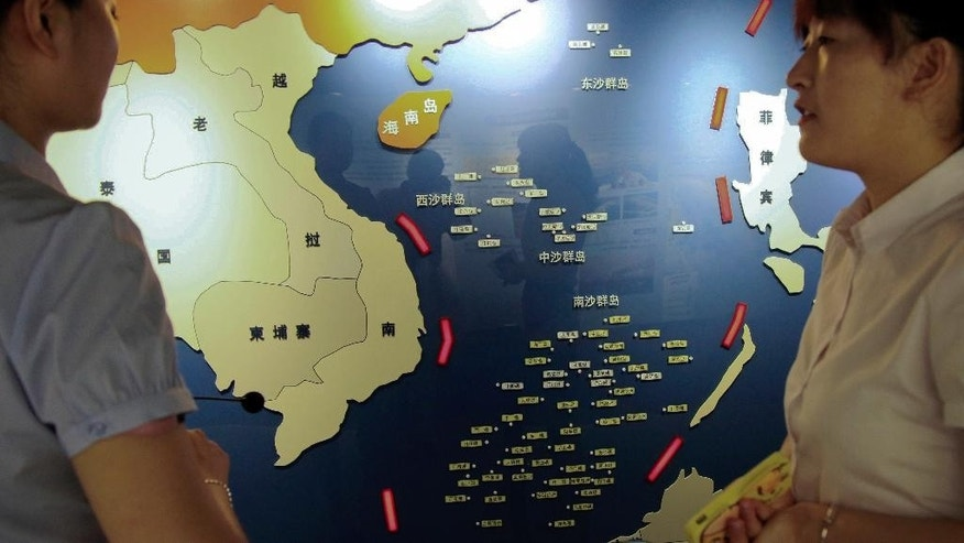 """In this Tuesday, July 12, 2016 photo, workers chat near a map of South China Sea on display at a maritime defense educational facility in Nanjing in east China's Jiangsu province. China blamed the Philippines for stirring up trouble and issued a policy paper Wednesday calling the islands in the South China Sea its """"inherent territory,"""" a day after an international tribunal said China had no legal basis for its expansive claims. (Chinatopix via AP)"""