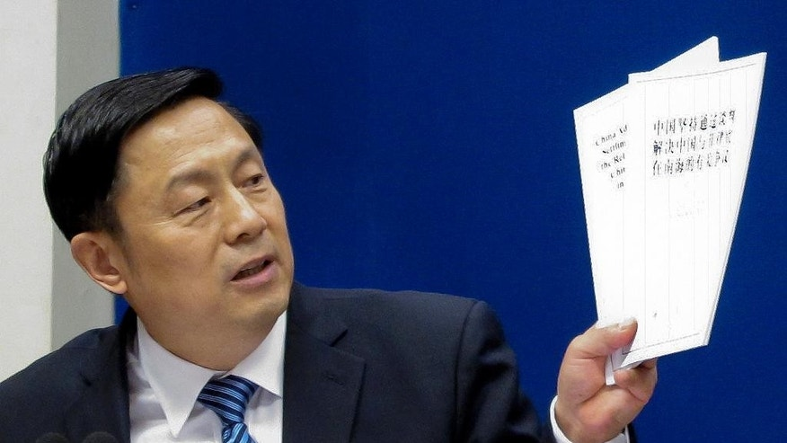 """State Council Information Office spokesman, Guo Weimin holds up white policy paper on South China Sea during a press briefing at the State Council Information Office in Beijing, Wednesday, July 13, 2016. China blamed the Philippines for stirring up trouble and issued a policy paper Wednesday calling the islands in the South China Sea its """"inherent territory,"""" a day after an international tribunal said China had no legal basis for its expansive claims. (AP Photo/Gillian Wong)"""