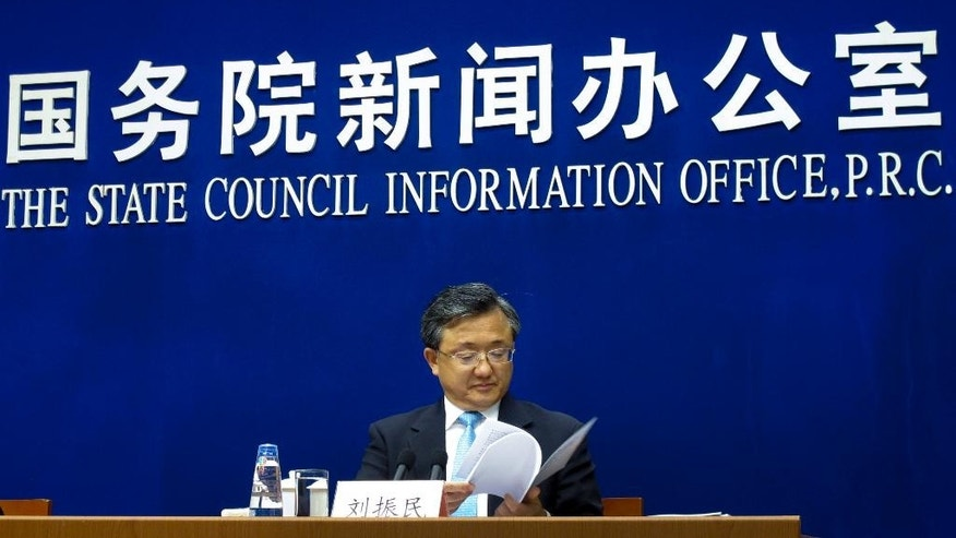 """China's Vice Foreign Minister Liu Zhenmin looks at the white policy paper on South China Sea during a press briefing at the State Council Information Office in Beijing, Wednesday, July 13, 2016. China blamed the Philippines for stirring up trouble and issued a policy paper Wednesday calling the islands in the South China Sea its """"inherent territory,"""" a day after an international tribunal said China had no legal basis for its expansive claims. (AP Photo/Gillian Wong)"""