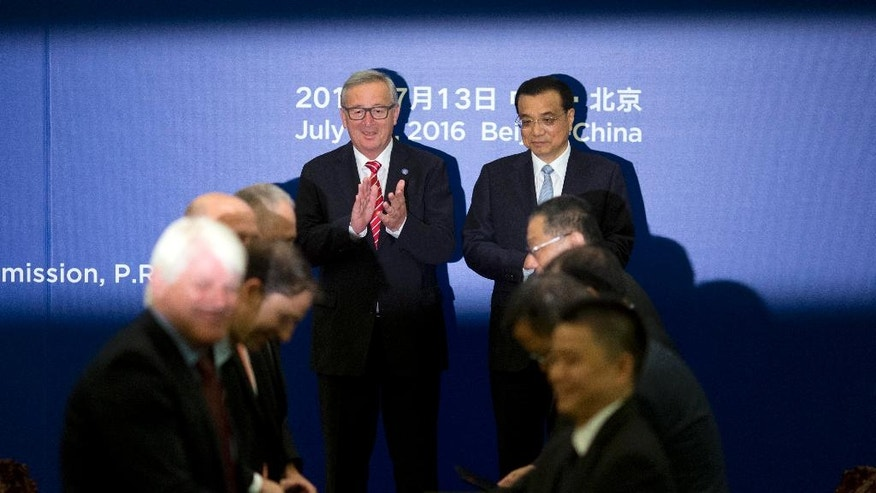 Chinese Premier Li Keqiang, center right, and European Commission President Jean-Claude Juncker, center left, applaud during a signing ceremony between Chinese and European Union officials at the Great Hall of the People in Beijing, Wednesday, July 13, 2016. (AP Photo/Ng Han Guan, Pool)