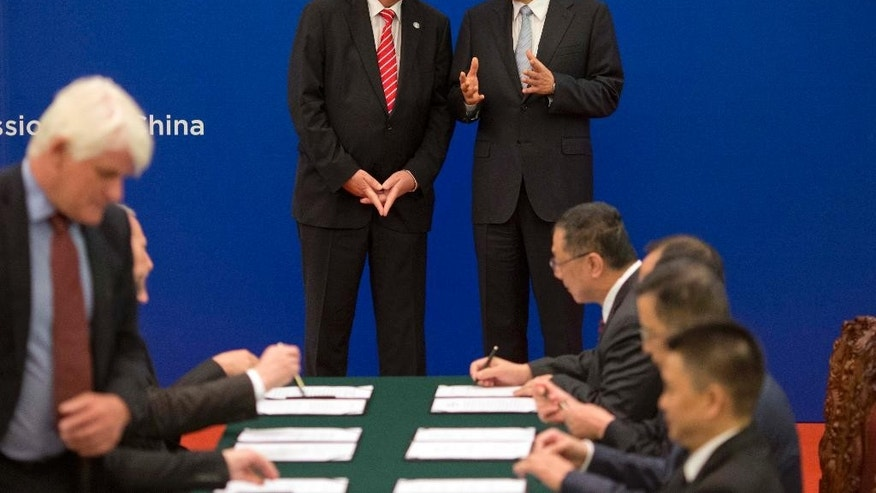 Chinese Premier Li Keqiang, center right, and European Commission President Jean-Claude Juncker chat as Chinese and European Union officials take part in a signing ceremony at the Great Hall of the People in Beijing, Wednesday, July 13, 2016. (AP Photo/Ng Han Guan, Pool)