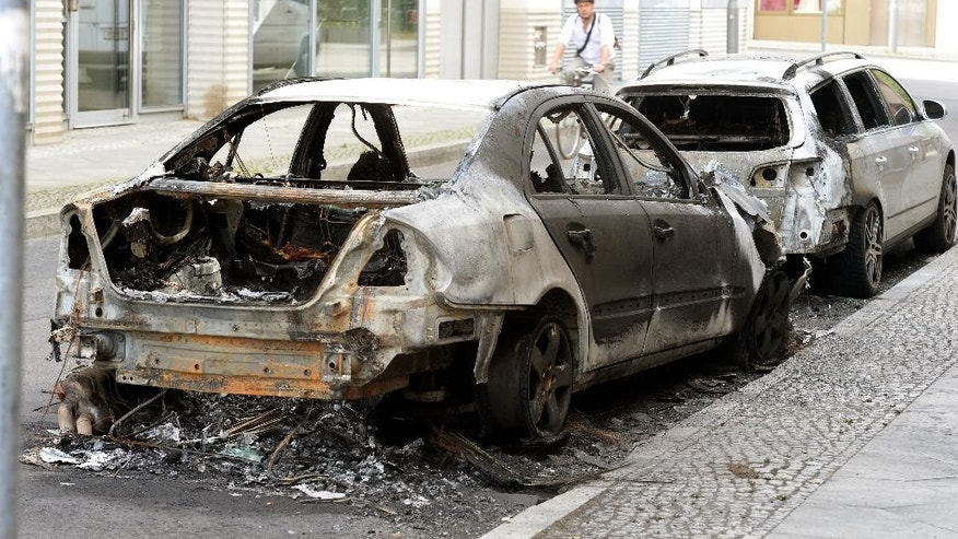 Destroyed cars stand in a street in Berlin Sunday July 10, 2016.  Police say more than 120 officers were injured and some 86 demonstrators were detained during leftist riots Saturday in the German capital which police calls the most aggressive and violent protests in the last five years. Berlin police said in a statement Sunday leftist protesters threw bottles, cobble stones and fireworks, destroyed cars and attacked officers with fists and kicks. It was not clear how many rioters were injured in the quarrels. (Maurizio Gambarini/dpa via AP)