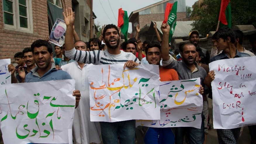 """Kashmiri villagers carry placards and shout freedom slogans during a protest on the outskirts of Srinagar, Indian controlled Kashmir, Wednesday, July 13, 2016. Curfew imposed in the disputed Himalayan region continues for the fifth consecutive day to suppress anti-India violence following the Friday killing of Burhan Wani, chief of operations of Hizbul Mujahideen, Kashmir's largest rebel group. Placards in Urdu read, from right, """"We have nourished Kashmir with blood. It belongs to us,"""" """"This is our nation we will decide its fate,"""" and """"Freedom is our right."""" (AP Photo/Dar Yasin)"""
