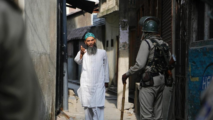 A Kashmiri man speaks with Indian soldiers for permission to cross a road during curfew in Srinagar, Indian controlled Kashmir, Wednesday, July 13, 2016. Curfew imposed in the disputed Himalayan region continues for the fifth consecutive day to suppress anti-India violence following the Friday killing of Burhan Wani, chief of operations of Hizbul Mujahideen, Kashmir's largest rebel group. ( AP Photo/Mukhtar Khan)