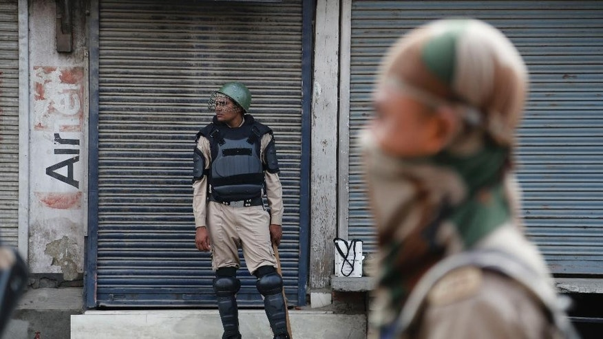 Indian paramilitary soldiers stand guard during curfew in Srinagar, Indian controlled Kashmir, Wednesday, July 13, 2016. Curfew imposed in the disputed Himalayan region continues for the fifth consecutive day to suppress anti-India violence following the Friday killing of Burhan Wani, chief of operations of Hizbul Mujahideen, Kashmir's largest rebel group. ( AP Photo/Mukhtar Khan)