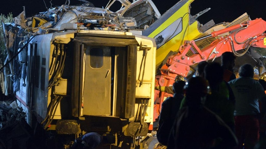 Rescuers work on the scene of a train accident after two commuter trains collided head-on near the town of Andria, in the southern region of Puglia, killing several people, Tuesday, July 12, 2016.  (AP Photo/Gaetano Lo Porto)