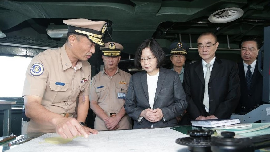 In this image taken and made available by the Taiwan Presidential Office on Wednesday, July 13, 2016, Taiwan's President Tsai Ing-wen, center right, reviews nautical charts aboard a Taiwan Navy ship before it sets out to patrol in the South China Sea from the naval base in the southern port city of Khaohsiung, Taiwan. Taiwan's Ministry of National Defense said Wednesday it will continue to send planes and ships to the South China Sea to carry out patrol missions and defend Taiwan's territory and sovereignty despite the Permanent Court of Arbitration's ruling in The Hague, said the Central News Agency.  (Taiwan Presidential Office via AP)