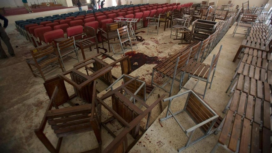 FILE -- In this Dec. 17, 2014 file photo, chairs are upturned and blood stains the floor at the Army Public School auditorium a day after Taliban gunmen stormed the school and killed some 150 people, mostly children, in Peshawar, Pakistan. The Pakistani army said Wednesday, July 13, 2016 that the mastermind of the 2014 attack on an army-run school has been killed in a U.S. drone strike. A Pakistani military spokesman says that a U.S. Army general confirmed the death of Taliban leader Khalifa Umar Mansoor in a phone call to Pakistan's army chief. (AP Photo/B.K. Bangash, File)